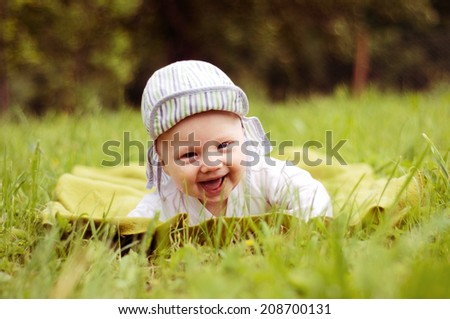 Happy baby lying on the grass  - stock photo
