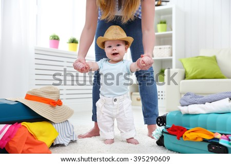 happy baby makes the first step with mother are packing their bags to vacation, travel - stock photo
