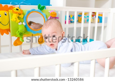 Happy baby on crib - stock photo