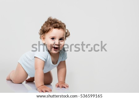 Happy baby on gray background.