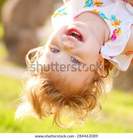Happy baby playing and laughing upside down. Summer holidays concept. - stock photo
