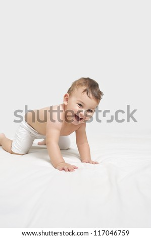 Happy baby playing on a towel - stock photo