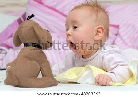 Happy baby playing with a toy - stock photo