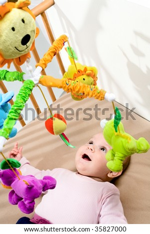 Happy baby playing with bed side toy, smiling. - stock photo