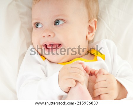 happy baby playing with his feet - stock photo