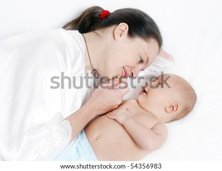 Happy baby playing with mother - stock photo
