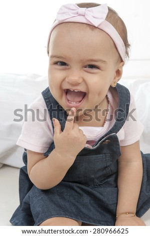 happy baby point at her mouth - stock photo