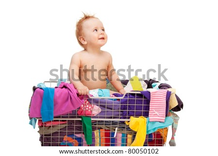 Happy baby sitting  in basket with clothes - stock photo
