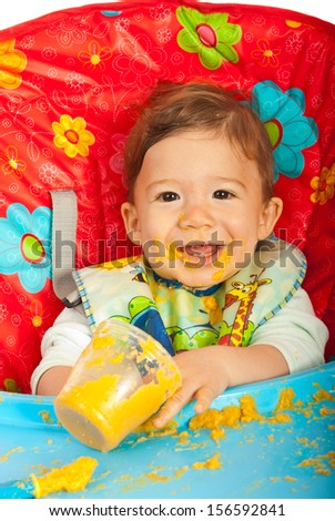 Happy baby sitting in chair and eating vegetables puree - stock photo