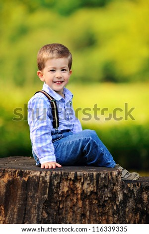 happy baby sitting on a stump. Sunny summer day - stock photo