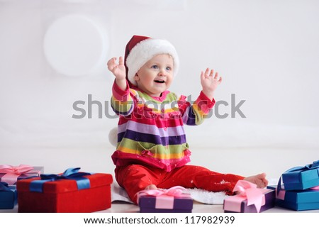 Happy baby sitting on the floor near boxes with gifts. Girl in santa hat. Christmas. The child is happy and raised his hands. - stock photo