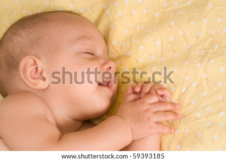 happy baby sleeping on a yellow background - stock photo