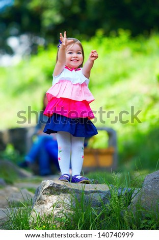 happy baby stretching hands, green outdoors