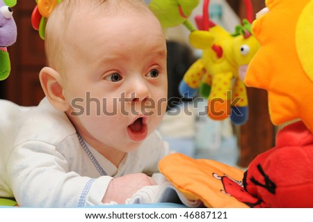 Happy baby surrounded by toys - stock photo