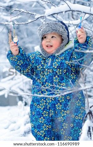 Happy baby takes Christmas toys in the winter garden - stock photo