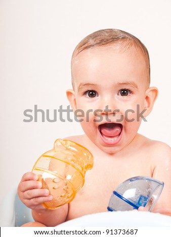 Happy Baby taking a bath in a bathtub with toys - stock photo