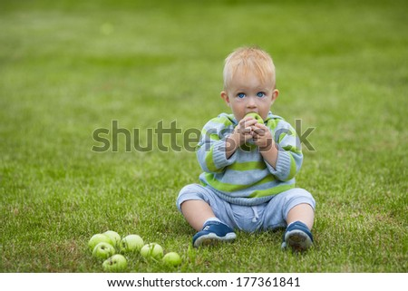 Happy baby with apple sitting on the grass. Happy smile.