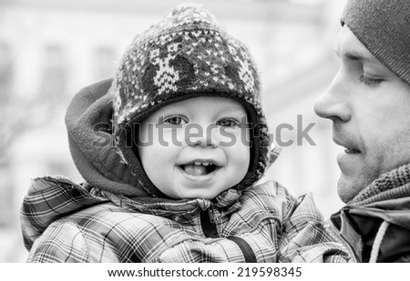 happy baby with his father outdoors in winter ( black and white ) - stock photo