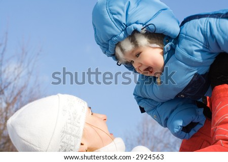 Happy baby with mother on blue sky. Spring - stock photo
