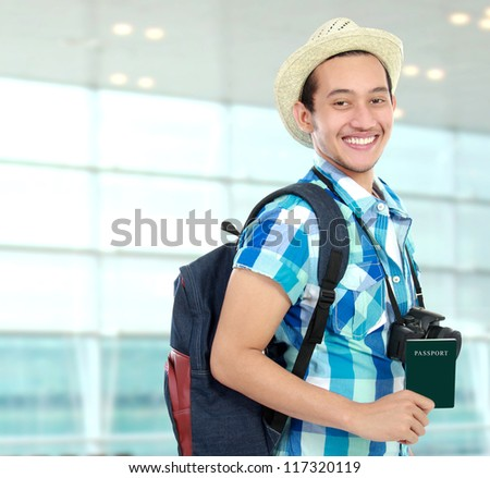 Happy backpacker at the airport terminal holding passport - stock photo