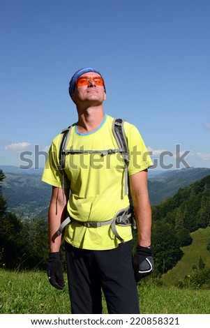 Happy backpacker on a mountain pass - stock photo