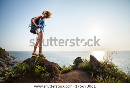 Happy backpacker standing on top of a hill at sunny day - stock photo