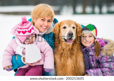 Happy baeutiful family on a winter walk with the dog