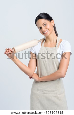 Happy baker chef in apron holding a rolling pin