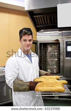 Happy baker showing his baguettes to the camera standing in his kitchen - stock photo