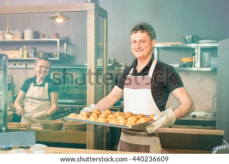 Happy baker showing tray of fresh croissant in the kitchen of the bakery - stock photo
