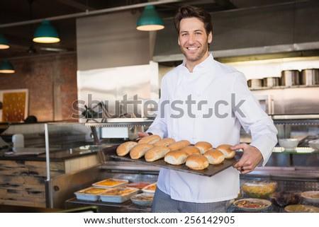 Happy baker showing tray with bread at the bakery - stock photo