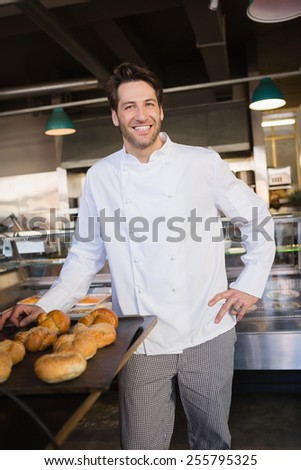 Happy baker standing near tray with bread at the bakery - stock photo