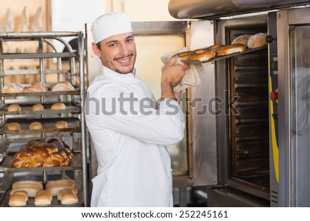 Happy baker taking out fresh bagels in the kitchen of the bakery - stock photo