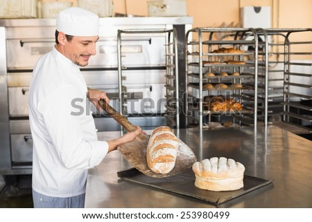 Happy baker taking out fresh loaf in the kitchen of the bakery - stock photo