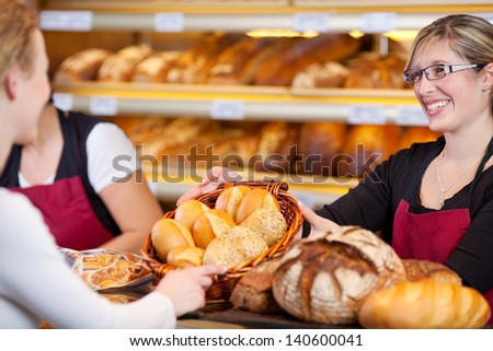 Happy bakery worker giving breadbasket to female customer - stock photo