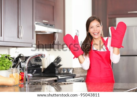 Happy baking cooking woman standing in her new kitchen smiling cheerful wearing apron and oven mitts ready to bake. Beautiful young mixed race Caucasian / Chinese woman at home. - stock photo