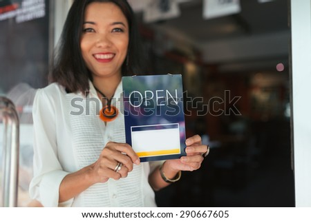 Happy bar owner holding open sign, focus on foreground - stock photo
