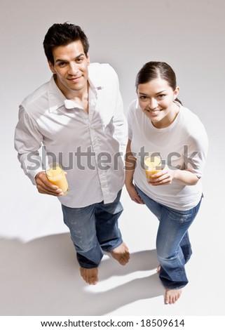 Happy barefoot couple drinking glasses of wholesome orange juice - stock photo