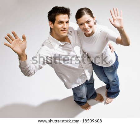 Happy barefoot couple waving a greeting - stock photo