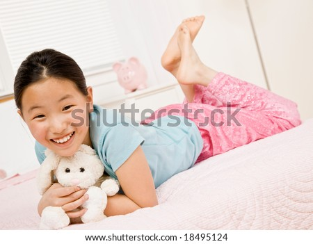 Happy, barefoot girl laying on bed with stuffed animal