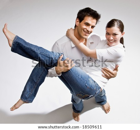 Happy barefoot man romantically carrying wife in his arms - stock photo
