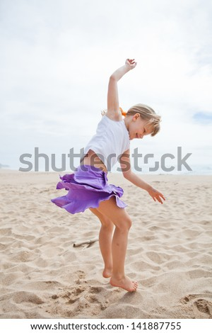 Happy barefoot young girl in purple skirt and white top jumping in sand on beach