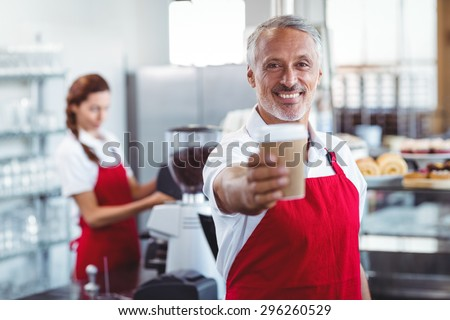 Happy barista giving take-away cup at the cafe - stock photo