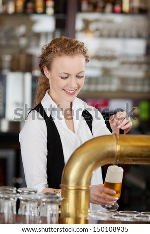 Happy barmaid pouring draft beer standing behind the counter in a bar or pub filling a pint glass - stock photo
