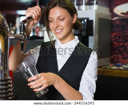 Happy barmaid pulling a pint of beer in a bar - stock photo