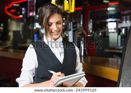 Happy barmaid writing in notepad in a bar - stock photo