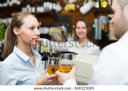 Happy bartender and guests couple with wine at bar counter. Focus on girl