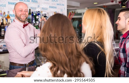 Happy bartender mixing cocktails in a shacker for a company at the bar - stock photo