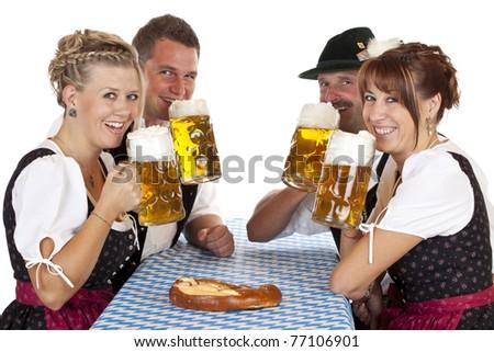 Happy Bavarian men and women drink Oktoberfest beer stein. Isolated on white background. - stock photo