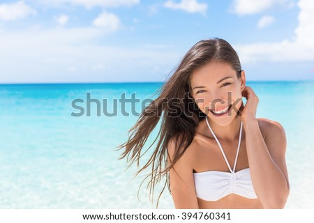 Happy beach Asian woman living a healthy lifestyle. Beautiful young mixed race girl smiling at camera wearing white bikini top on tropical Caribbean vacation with hair in the wind. - stock photo